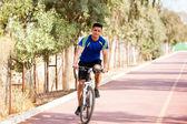 Young Latin man riding a bike — Stock Photo