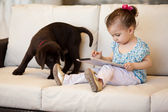 Girl with a dog and a tablet — Stock Photo