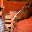 Girl feeding horse in ranch — Stock Photo #41009769