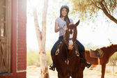 Woman riding a horse and smiling — Stock Photo