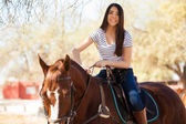 Woman riding her horse and petting him — ストック写真