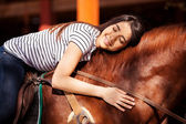 Brunette giving her horse a hug while riding him — Stock Photo
