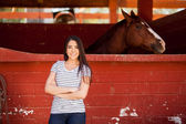 Woman standing next to her horse in a stable — Stock Photo