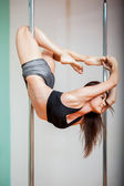 Woman holding a pose in a pole fitness class — Stock Photo