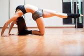 Kvinnan gör en sexig utgör i en pole fitness klass — Stockfoto