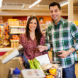 Cute young couple standing with a trolley with products in the store at checkout and man paying with credit card — Stock Photo