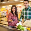 Cute young couple buying groceries with a credit card — Stock Photo #42681875