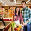 Cute young couple using a credit card at the store — Stock Photo