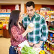 Cute young woman showing her husband what does she want to buy in the store — Stock Photo