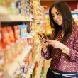Young woman looking and reading the food label — Stock Photo