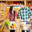 Happy couple shopping and flirting at the supermarket — Stock Photo