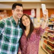Happy couple taking picture in the store — Stock Photo