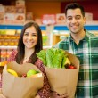 Happy couple with shopping bags at the store — Stock Photo #42682423