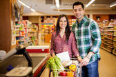 Cute  young couple standing with a trolley with products in the store at checkout — Stock Photo
