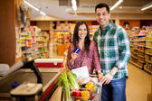 Cute  young couple using a credit card at the store — Foto de Stock