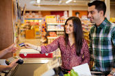Young couple using a credit card at the store — Foto de Stock