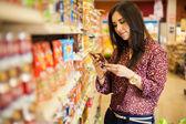 Ung kvinna söker och läser märkningen av livsmedel — Stockfoto