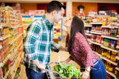 Happy couple kissing at the grocery store — Stock Photo