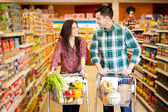 Happy couple shopping and flirting at the supermarket — Foto de Stock