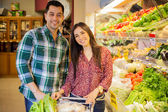 Happy Hispanic newlyweds doing some shopping together in a supermarket — Stock Photo