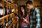 Happy couple deciding which kind of wine to buy — Stock Photo
