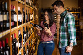 Happy couple choosing between many options of wine — Stock Photo