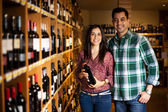 Cute couple buying a bottle of wine — Stock Photo