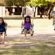 Happy little Latin girls having fun in a swing outdoors in summer — Stock Photo