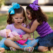 Pretty little girl telling her friend a secret while hanging out at a park — Stock Photo