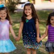 Three little girls smiling and holding hands in a park on a sunny day — Stock Photo