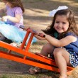 Sweet little girl and her friends having fun in a seesaw in a park and smiling — Stock Photo