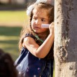 Pretty Hispanic little girl thinking what to draw with a chalk on a tree — Photo