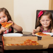 Pretty little Hispanic girls eating pizza together at home — Stock Photo #43226603