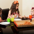 Cute little cousins enjoying pizza together at home — Stock Photo #43226627