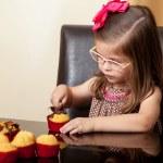 Beautiful little girl decorating cupcakes — Stock Photo #43226647