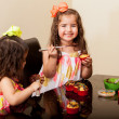 Little girl and her sister decorating some cupcakes — Stock Photo