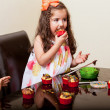 Cute little girl and her friends decorating and eating some cupcakes at home — Stock Photo