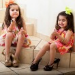 Happy little friends having fun trying on some lipstick and their moms' shoes — Stock Photo