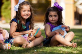 Pretty little girls having fun and playing with their dolls at a park — Stock Photo
