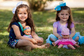 Ouple of beautiful girls playing with their dolls at a park — Stock Photo