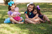 Beautiful little girl playing with her doll while ignoring her friends at a park — Stock Photo