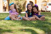 Pretty little girl playing with a doll and hanging out with her friends at a park — Stock Photo