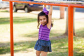 Pretty little girl climbing and hanging from some handlebars at a park — Stock Photo