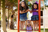 Cute group of little girls about to play in some handlebars at a park — Stock Photo