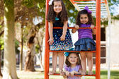 Beautiful little friends climbing some handlebars and having fun at a park — Stock Photo