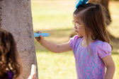 Beautiful little girl drawing with a chalk on a tree at a park — Stock Photo