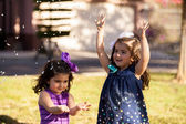 Little sisters having fun with some foam that looks like snow at a park — Stock Photo