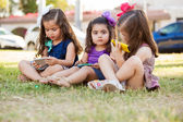 Pretty little girls playing with their smart phones while hanging out at a park — Stock Photo