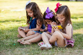 Cute little sisters playing with their own phone and ignoring each other at a park — Stock Photo