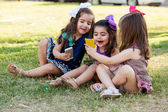 Funny little girls sharing some stuff from their smart phones and having fun — Stock Photo